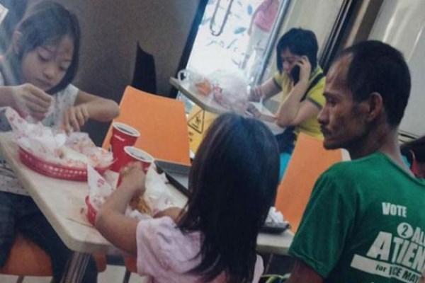 Hình ảnh người cha khắc khổ lặng lẽ nhìn 2 con gái nhỏ say sưa ăn gà rán khiến nhiều người rơi nước mắt