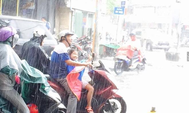 Bức ảnh ấm lòng trong Ngày của Cha: Bố uớt sũng nhường áo mưa, miễn là con đừng ốm nhé!