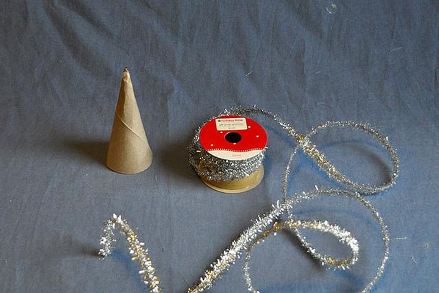 Quấn chặt tay dây kim tuyến quanh cây thông Noel, dùng keo để cố định kim tuyến không bị xộc xệch