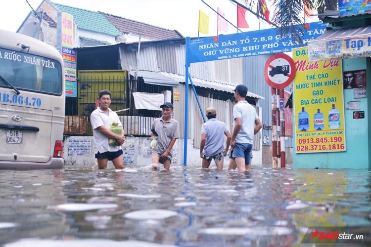 Mưa ngập lịch sử ở TP. HCM: Người dân kết bè thả ra đường, thích thú túm tụm chụp ảnh vui chơi giữa biển nước - Ảnh 7