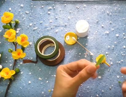 Cắt giấy nhún lá xanh nhỏ làm đài hoa