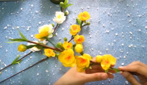 Nối từng cành hoa lá kẽm với nhau bằng băng keo sáp nâu làm thân, cành hoa mai