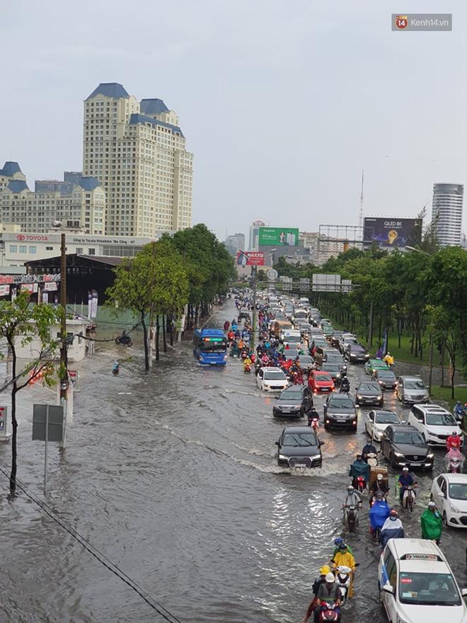 Đường phố Sài Gòn ngập lênh láng sau cơn mưa lớn, người dân khổ sở dắt xe lội nước trên đường - Ảnh 1