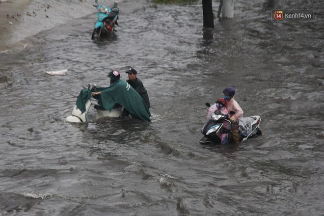 Đường phố Sài Gòn ngập lênh láng sau cơn mưa lớn, người dân khổ sở dắt xe lội nước trên đường - Ảnh 4