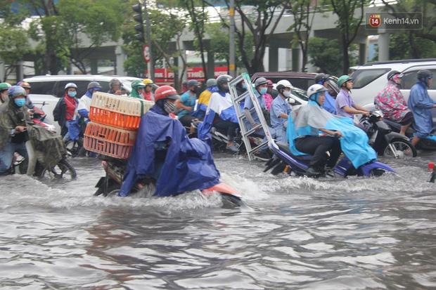 Đường phố Sài Gòn ngập lênh láng sau cơn mưa lớn, người dân khổ sở dắt xe lội nước trên đường - Ảnh 6