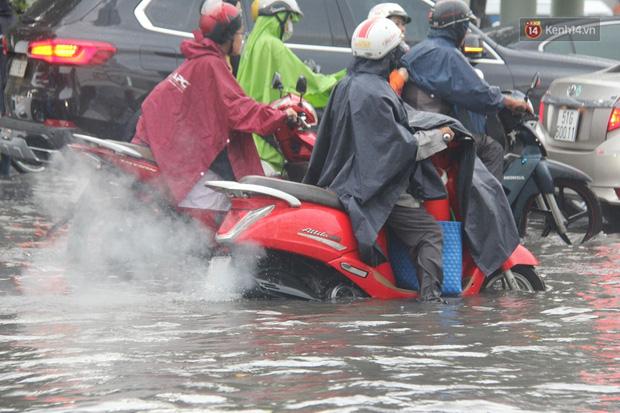 Đường phố Sài Gòn ngập lênh láng sau cơn mưa lớn, người dân khổ sở dắt xe lội nước trên đường - Ảnh 9