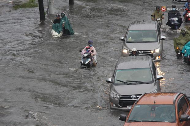 Đường phố Sài Gòn ngập lênh láng sau cơn mưa lớn, người dân khổ sở dắt xe lội nước trên đường - Ảnh 10