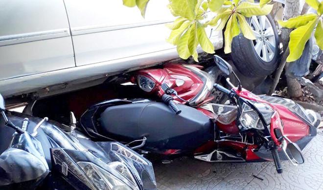 Lùi ôtô từ nhà ra đường, nữ tài xế cuốn 4 xe máy vào gầm - Ảnh 1