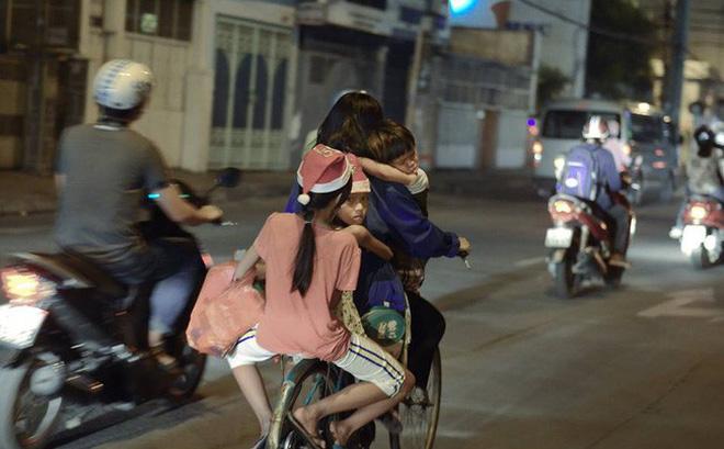 Khoảnh khắc lay động: Giáng sinh về sớm trên mái đầu trẻ thơ, mẹ chở 3 con trên chiếc xe đạp cũ - Ảnh 1