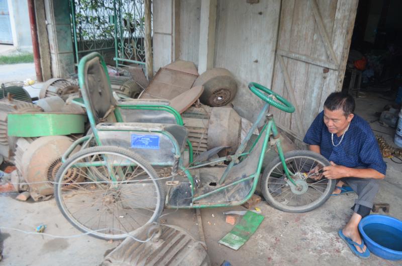 Người đàn ông liệt 2 chân chế xe cho người khuyết tật - Ảnh 1