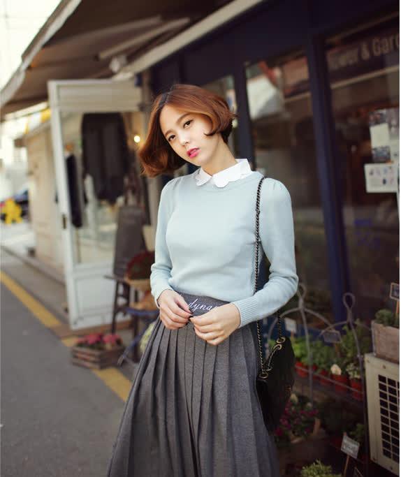 Mix chiếc áo trắng cổ cách điệu với áo len màu pastel váy xòe dáng dài cuốn hút