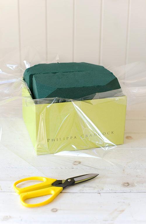 Đặt miếng xốp vào bên trong và lấy kéo cắt bỏ phần giấy bóng kính thừa bên ngoài