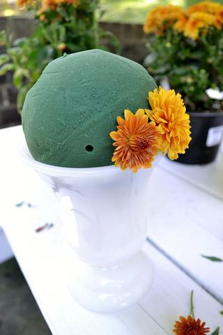 Lần lượt cắm hoa từ sát miệng bình lên trên đỉnh của quả cầu miếng xốp