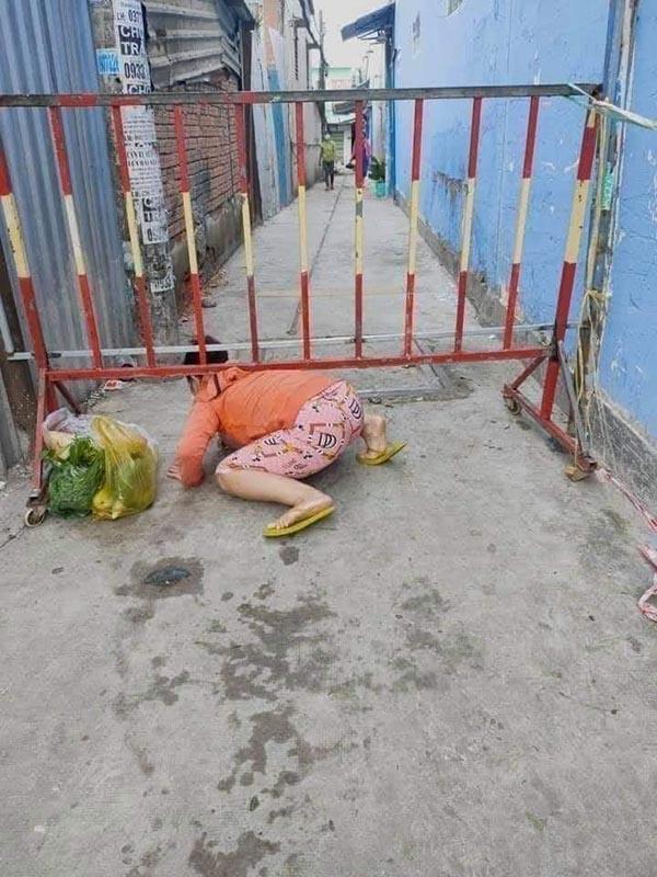 Xôn xao nhóm phụ nữ 'luồn lách' lén ra khỏi khu phong tỏa để đi chợ: Người 'bò ra đất', kẻ bất chấp trèo qua rào? - Ảnh 1