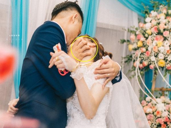 Cô dâu chú rể hôn đắm đuối trên sân khấu, bàn tay của chú rể đặt ở nơi