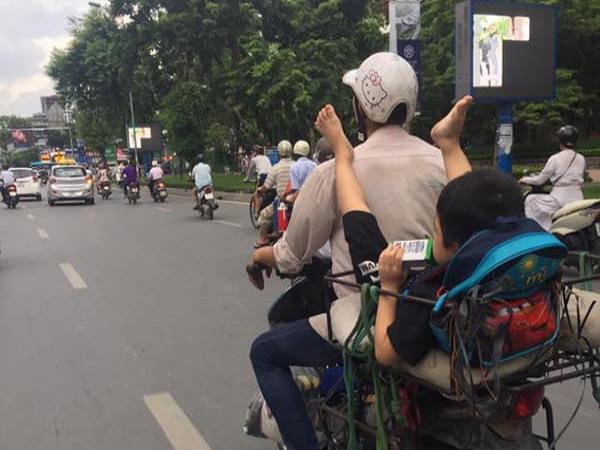 Bức ảnh cậu bé ngồi vắt vẻo ở yên sau, gác 2 chân lên vai mặc cho bố đang chạy xe gây tranh cãi