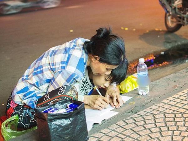 Bức ảnh khiến hàng triệu trái tim xúc động: Mẹ nghèo nắn nót từng chữ dạy con bên vỉa hè