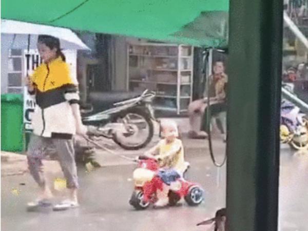 """Người phụ nữ thản nhiên che ô bỏ mặc đứa trẻ dầm mưa tầm tã, người """"ướt như chuột lội"""" khiến dân mạng tranh cãi"""