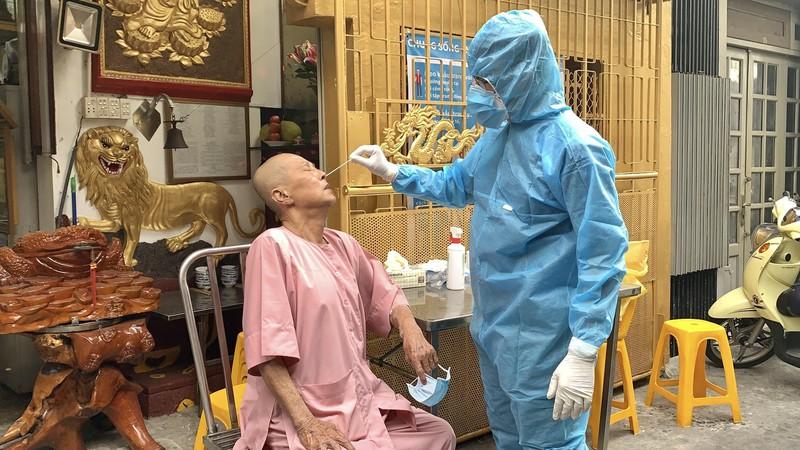 Lấy mẫu xét nghiệm COVID-19 người đi chùa tại TP.HCM - Ảnh 1