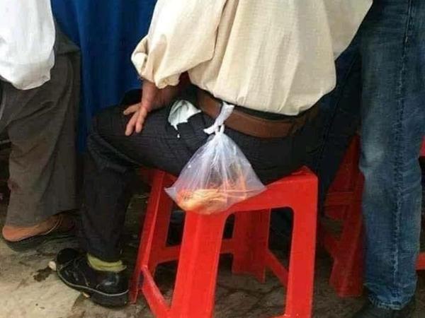 Đi ăn cỗ sợ bị mất túi tôm thơm ngon để phần cho con, ông bố buộc luôn vào lưng quần 'cho chắc '