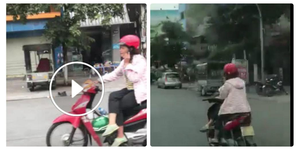 Người phụ nữ tay phải cầm lái, tay trái nghe điện thoại, ngồi vắt chân một bên