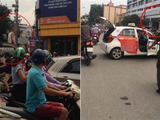 """Hà Nội: Đi vào đường cấm bị CSGT nhắc nhở, tài xế taxi leo lên nóc ô tô """"ăn vạ"""""""