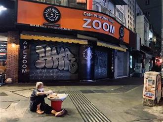 Bức ảnh xúc động: Cụ bà ngồi một mình giữa phố vắng, cố bán hết mâm bánh để mưu sinh