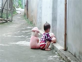 Hình ảnh bé gái vừa tròn tuổi tha thẩn chơi một mình khi mẹ chăm em khiến trái tim những mẹ đông con nhói đau