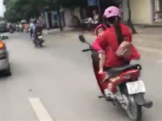 Clip mẹ vừa bế con vừa gác chân chạy xe máy gây phẫn nộ
